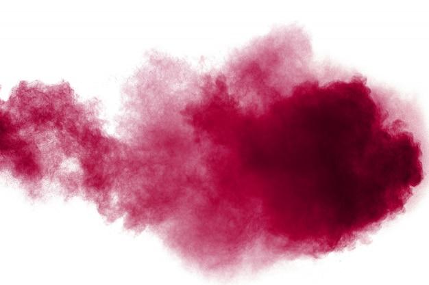 白い背景の上に飛び散った抽象的な赤い塵。赤い粉の爆発。赤い粒子の飛散の動きを凍結します。