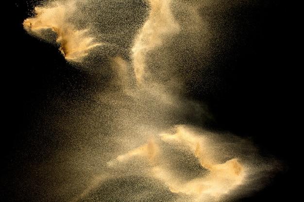 黒に分離された砂の爆発。砂塵飛沫の動きを凍結します。