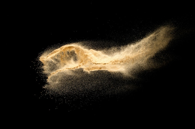 黒の背景に分離された川の砂の爆発を乾燥させます。砂の雲を抽象化します。暗い背景に対して茶色の色の砂のスプラッシュ。