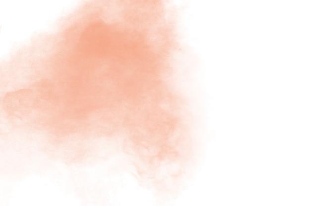 白い背景の上の抽象的な光オレンジ粉の爆発。明るいオレンジ色のダスト粒子スプラッシュの動きを凍結します。