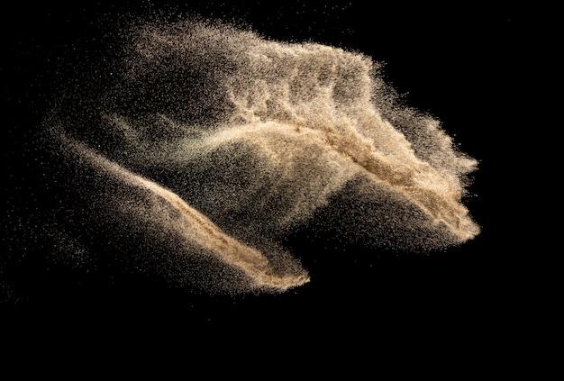 Брайн покрасил всплеск песка. взрыв песка реки реки изолированный на черной предпосылке. абстрактное облако песка.