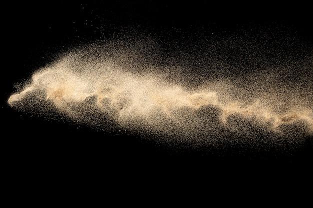 茶色の砂のスプラッシュ。黒の背景に分離された乾燥した川の砂の爆発。抽象的な砂の雲。
