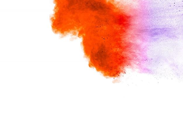 白い背景の上のオレンジブルーパウダー爆発。オレンジブルー色のほこりスプラッシュ雲。