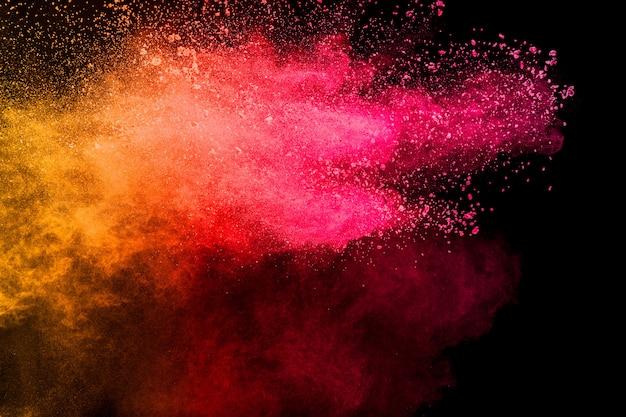 Заморозьте движение брызг частиц пыли красного желтого цвета.