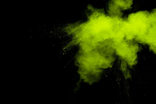 Облако взрыва порошка зеленого цвета на черной предпосылке. зеленый выплеск пыли на предпосылке.