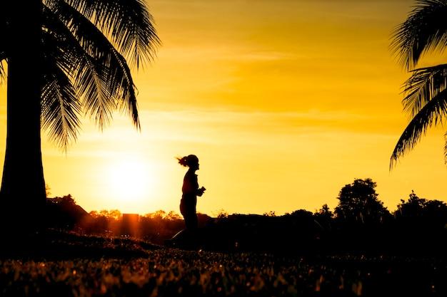 夕日の公園での運動のための歩行とジョギングのシルエット