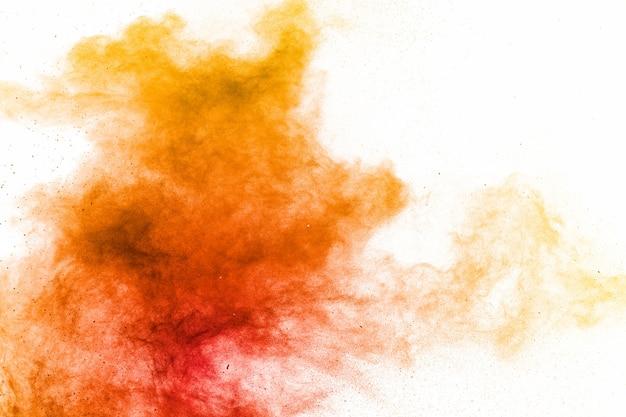 白い表面に抽象的な黄色オレンジ色の粉末の爆発