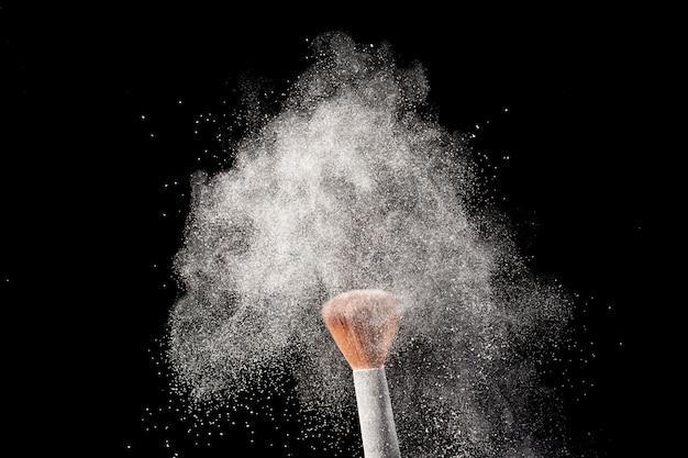 メイクアップブラシほお紅白い背景で隔離の白い粉のスプラッシュ。