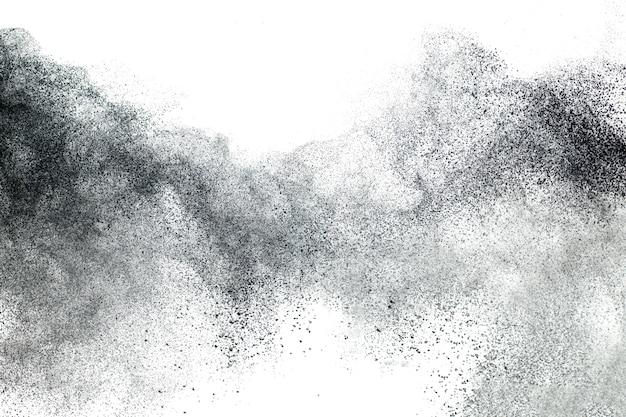白い背景の黒い粉の爆発。黒いほこりの粒子が跳ねます。