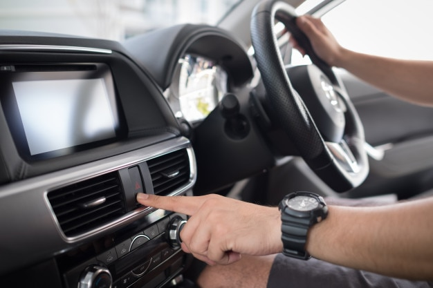 男は車のボタンを押す、現代の車のインテリア