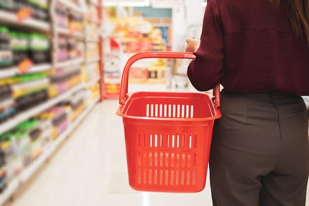 スーパーマーケットのバスケットを持つ若い女性のトリミング