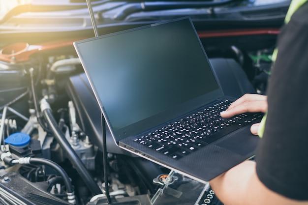 電気診断装置を使用して車を調整するエンジニアのメカニックを閉じる