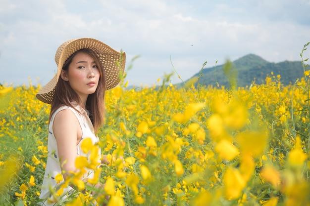 黄色の畑で夏を楽しんでいる若い女性