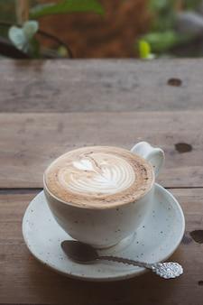 Чашка кофе на завтрак на столе. добавлен винтажный тон.