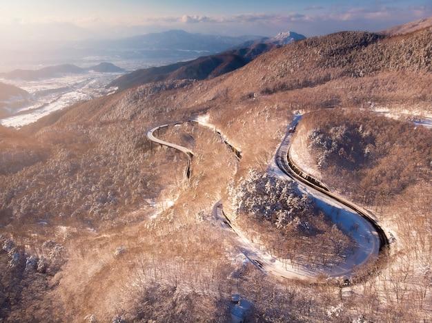 山の冬の森とカーブの道の上から見る