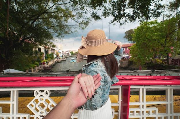 Задняя часть женщины, держащей руку человека, ведущего для путешествия в малакке, малайзия