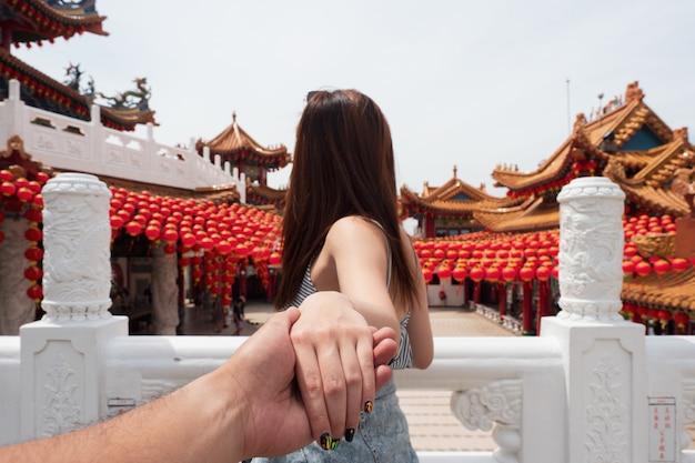Молодая женщина, держащая мужское ручное путешествие в храме теан хоу в куала-лумпуре, малайзия