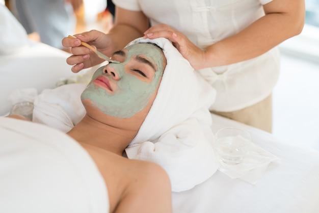 Женский терапевт, делающий уход за лицом / лечение, добавляет влагу к коже