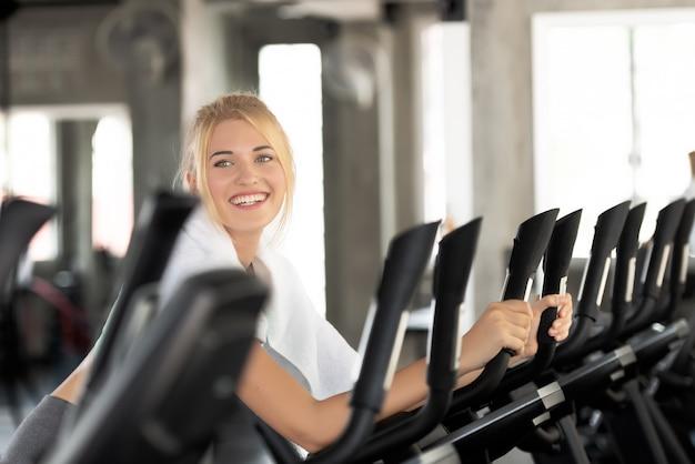 Кавказские женщины счастливы улыбаться во время тренировки на велосипеде в спортзале.