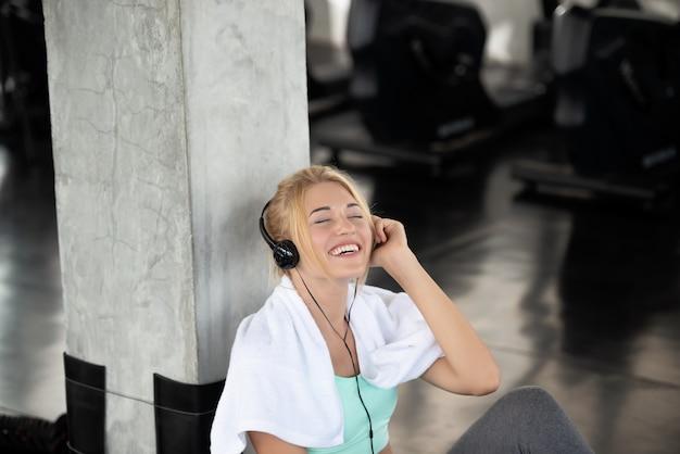 白い若い女性は笑顔幸せ使用電話耳の音楽です