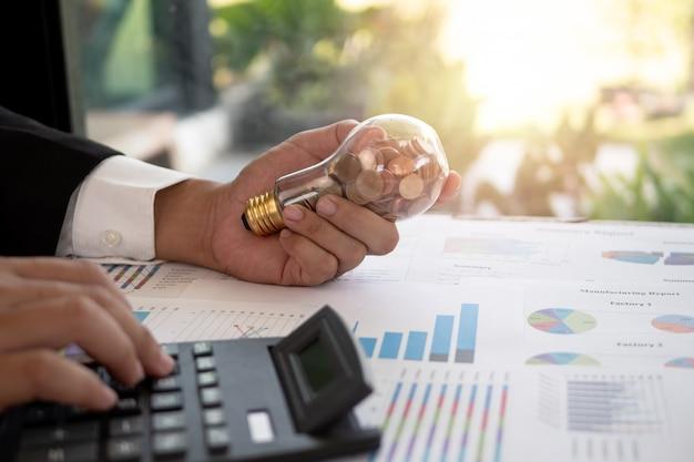 ビジネスマンの手コインと電球を保持します。コスト削減とエネルギー削減の考え方