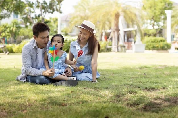 アジアの幸せな家族。自然な日差しの公園で父、母と娘。家族休暇の概念。