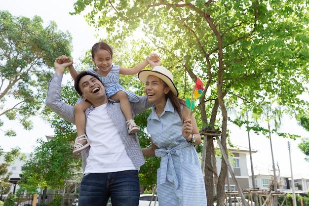 アジアの幸せな家族。父は娘に自然光と家の公園でおんぶをしました。家族休暇の概念