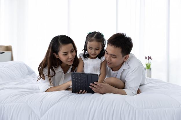 デジタルタブレットを持つアジアの家族