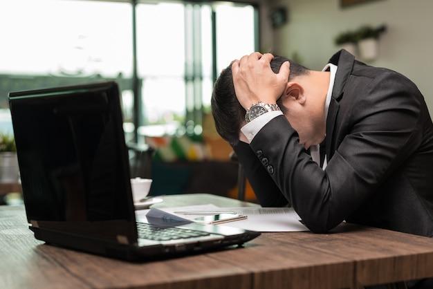 ラップトップとコーヒーショップに座って挫折したアジア人のビジネスマンを挫折