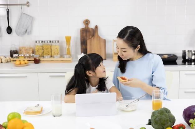 母と娘は朝食を食べて、タブレットでメディアを見て