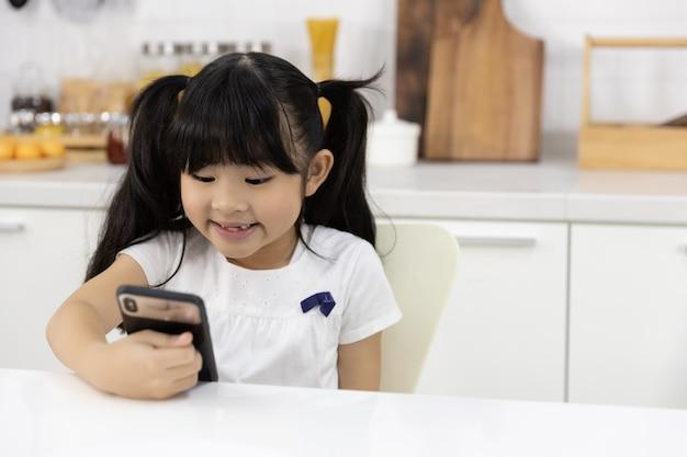幸せなアジアの女の子は、スマートフォンを楽しむ