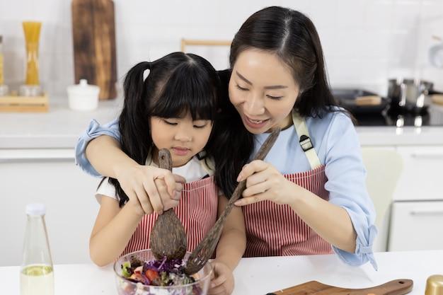 母と少女はボウルにサラダを準備しています