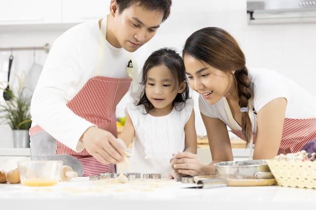 父、母と娘は台所でクッキーを準備しています