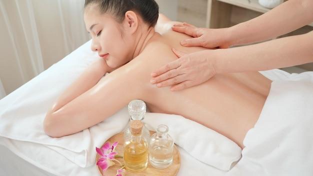 Молодая азиатская женщина получая расслабляющий массаж масла на салоне курорта красоты. массаж для здоровья
