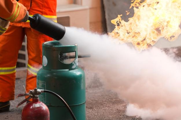 Инструктор показывает, как использовать огнетушитель. газовые баки с огнем.