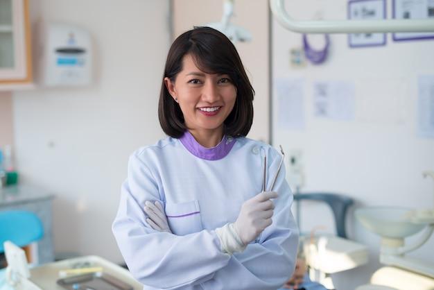 Азиатский женщина-стоматолог стоял, улыбаясь и держа зубного инструмента в больнице.