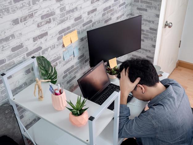 アジアの男性が彼の部屋、マンションでラップトップコンピューターでの作業します。