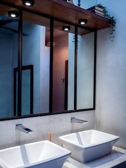 Современный белый умывальник и кран в ванной комнате.