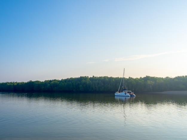 緑の森と青い空に青い湖でヨットします。