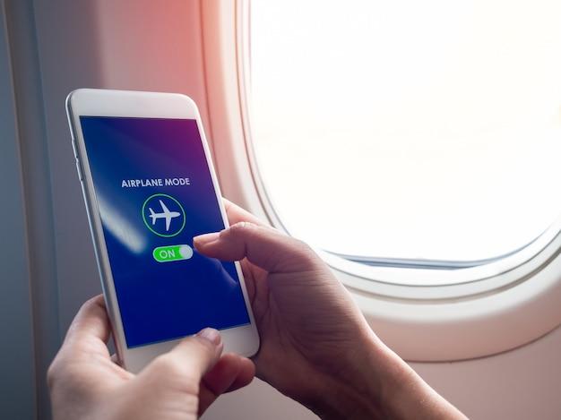 フライトモードのコンセプト。白いスマートフォンを持っている手と飛行機の窓の近くの画面で飛行機モードをオンにしました。