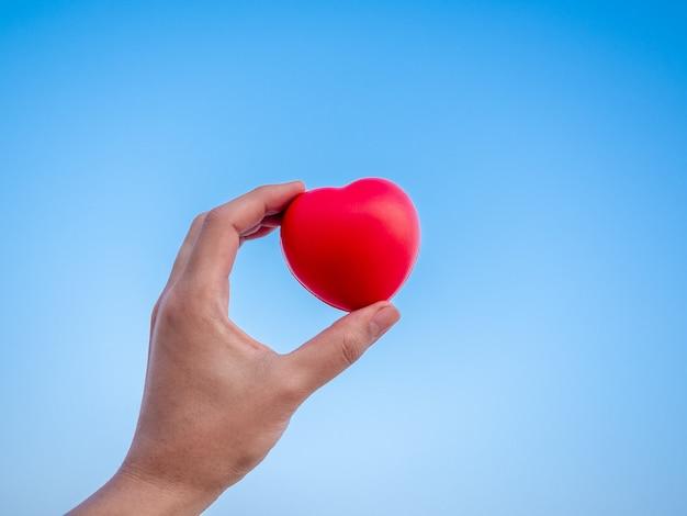 Красное сердце в руке на голубом небе