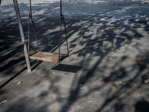 Старые одинокие деревянные качели на время заката с света и тени.