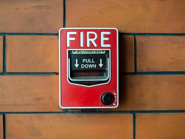 レンガの壁に赤い手動火災警報
