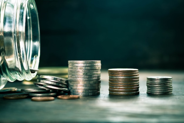 ウッドの背景上のコインのコンセプトは、将来のためにお金を節約します。