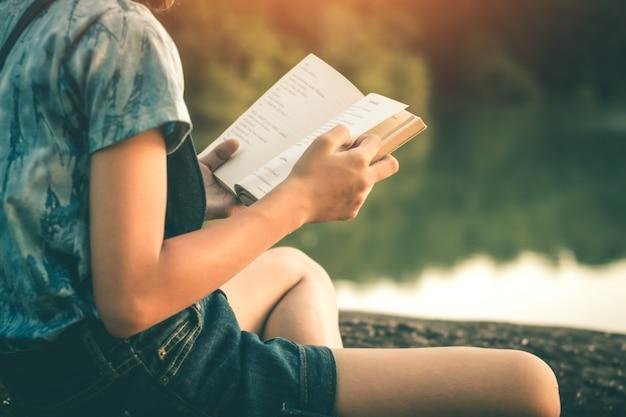 女性は静かな自然の中で本を読み、コンセプトは本を読みます。