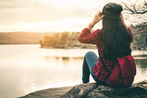 女性旅行者は、休日に静かなシーンで美しい自然の音楽を聴きます。