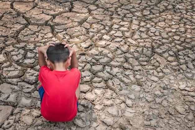 乾燥した地面に子供を悲しませる、干ばつのコンセプト。