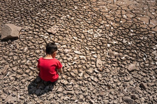 子供は悲しい、地面乾燥コンセプト干ばつ。