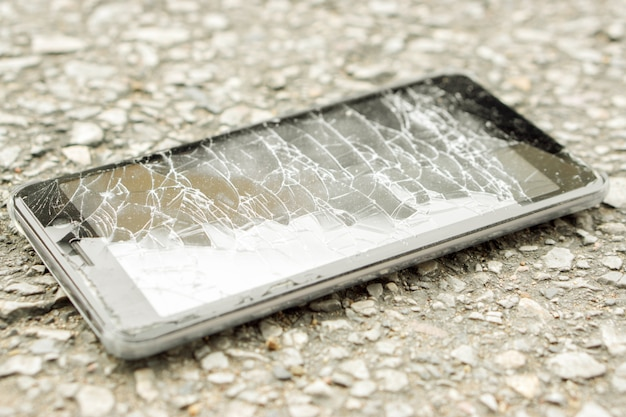 クローズアップ黒携帯電話の事故は道路と自然の太陽光で壊れたガラスに落ちる。