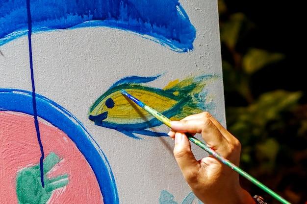 ブラシを保持している美術学生のクローズアップ手は、新しい美術教室の壁に描いて飾っています。